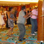 John loved dancing even by himself. He is dancing along with the crowd on the cruise.