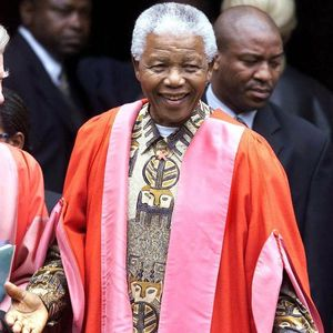 Former South Africa President Nelson Mandela smiles Wednesday, 5/2/01, before a ceremony at Magdalene College, Cambridge, England, where he was being made an Honorary Fellow. Around 100 students and staff had gathered to welcome Mandela and he donned the robes of a Doctor of Law of Cambridge University