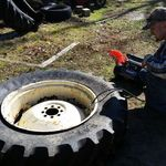 Changing his Dad's tractor tire..