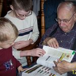 Joe looking through model train catalog with two great-grandsons, Nate and Ostyn
